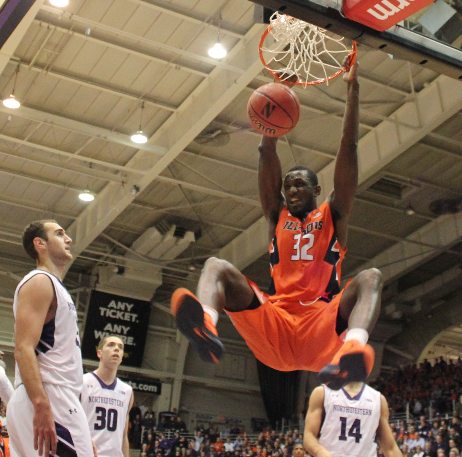 Alex Olah (left) and Bryant McIntosh (30) watch Illini Nnanna Egwu slam dunk at Welsh-Ryan Arena in Evanston